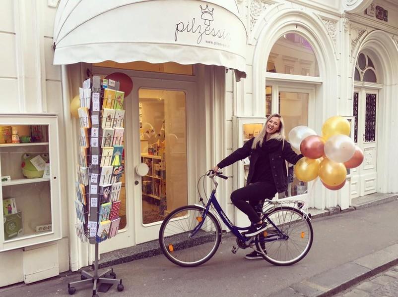 Kati Pilz auf einem Fahrrad mit Luftballons vor dem Geschäft Pilzessin